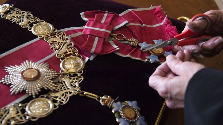 Diane Hatcher, a seamstress at Cleave Court Jewellers, sews medals and decorations conferred on the duke