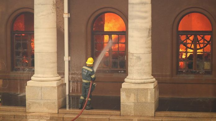 Firefighters tackle flames as University of Cape Town library burns after fire broke out on the slopes of Table Mountain in Cape Town