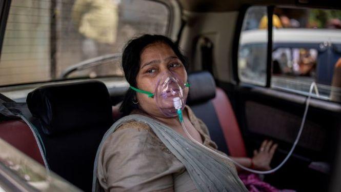 Yeni Delhi'de bir kadın oksijen yardımıyla nefes alıyor