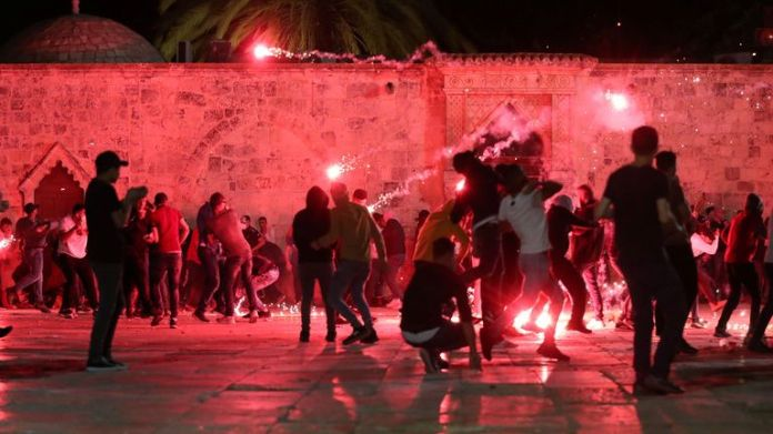 Palestinians react as Israeli police fire stun grenades during clashes in the compound that houses the Al-Aqsa Mosque, known to Muslims as the Noble Shrine and to Jews as the Temple Mount