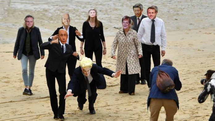 Members of the media take pictures of climate change activists wearing masks representing world leaders during a protest in St. Ives, on the sidelines of G7 summit in Cornwall, Britain, June 11, 2021. REUTERS/Dylan Martinez