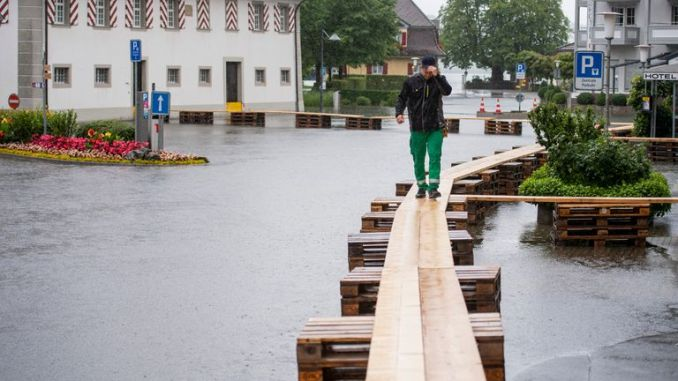 A person walks on a footbridge as the village square is covered with flood water in Stansstad. Pic: AP
