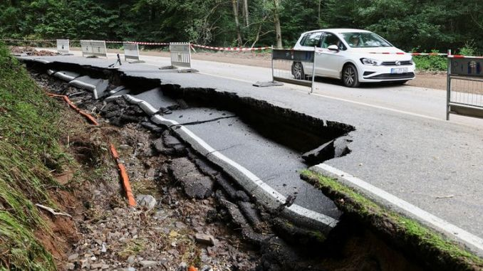 A road is pictured collapsed as the result of flooding in Bad Muenstreifel