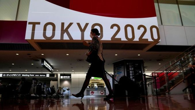 A flight attendant walks by a large display of Tokyo 2020 Olympics at Narita International Airport Thursday, July 15, 2021, in Narita, east of Tokyo. (AP Photo/Kiichiro Sato)