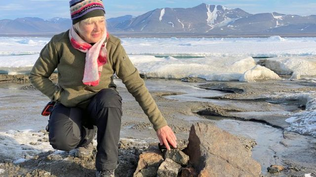 An undated handout image of Swiss entrepreneur Christiane Leister, creator of the Leister Foundation that financed an expedition which discovered a tiny island off the coast of Greenland which they say is the world's northernmost point of land, in front of a cairn in which expedition members left a message with details of their visit. Pic: Julian Charriere/via REUTERS THIS IMAGE HAS BEEN SUPPLIED BY A THIRD PARTY.