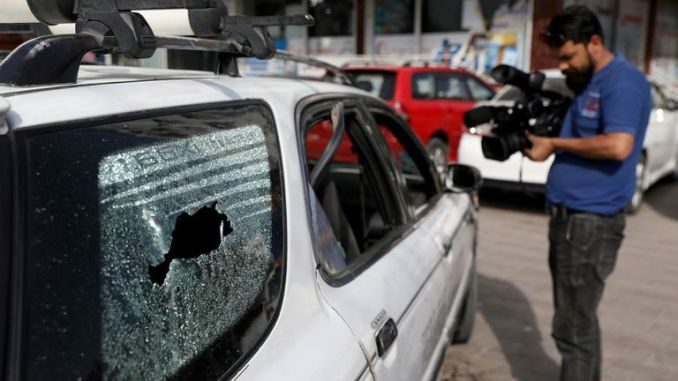 Afghan journalists films the vehicle in which director of Afghanistan's Government Information Media Center Dawa Khan Menapal was shot dead in Kabul. Pic: AP