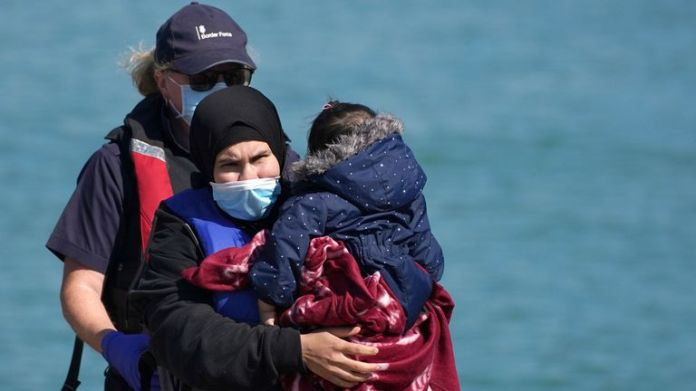 A Border Force officer helps a woman with a young child brought in to Dover, Kent, with a group of people thought to be migrants following a small boat incident in the Channel. Picture date:  y September 8, 2021.