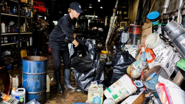 Beth Duchess sorts through damaged items at Ron Waters Automotive after heavy rains from storm Ida caused flooding in Oakdale, Pennsylvania