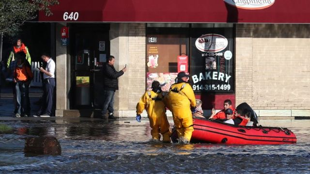 First responders pull residents in a boat following flooding from remnants of Tropical Storm Ida in Mamaroneck, New York