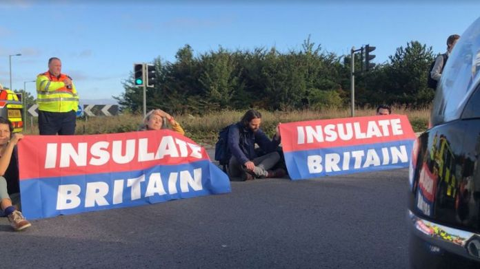 Protesters delay traffic at a roundabout on the M25. Pic: Insulate Britain