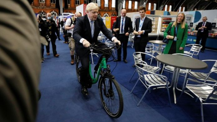 Britain's Prime Minister Boris Johnson sits on a bike as he visits a trade stall inside the conference venue at the annual Conservative Party conference, in Manchester, Britain, October 5, 2021. REUTERS/Phil Noble