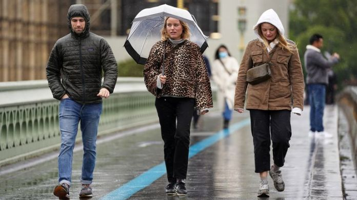 People walk across Westminster Bridge in the rain, in Westminster in London. Heavy rain and strong winds could bring flooding, travel disruption and power outages to parts of England and Scotland over the weekend.