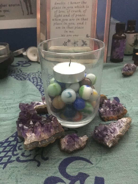 A chalice from Patricia Carson, made of a glass with marbles and a tea, surrounded by amethyst.