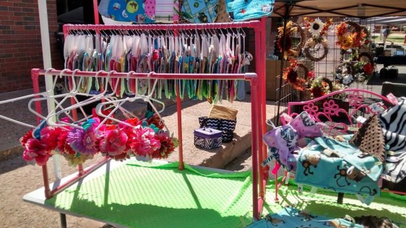 A booth  displaying colorful hair bows, ribbons and other handmade textiles
