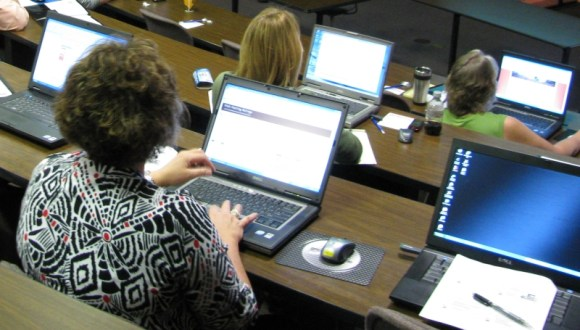 Audience members stare at laptops during a lecture