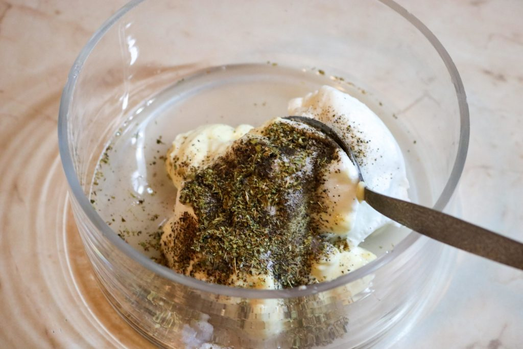 Mix the Greek yogurt, mayo, salt and pepper to taste, garlic powder, dried oregano and lemon juice