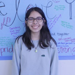 Junior Isabel Chequer smiles next to a banner donated to MSD. Photo by Anna Dittman
