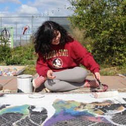 Senior Isabella Pfeiffer paints a mural for Astronomy Club in Marjory's Garden on Dec. 19. Photo by Nyan Clarke