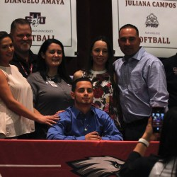 Senior Dianjelo Amaya celebrates signing to college with his family and administrators