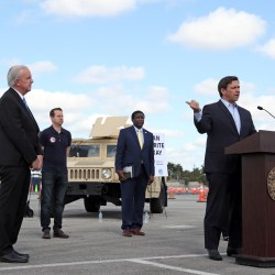 Governor Ron DeSantis speaks during a news conference at the COVID-19 drive-through testing site at Hard Rock Stadium in Miami Gardens on Monday, March 30, 2020. Standing socially distanced are the mayors of four South Florida Counties, Miami-Dade County Mayor Carlos Gimenez, Broward County Mayor Dale Holness, Palm Beach County Mayor David Kerner and Monroe County Mayor Heather Carruthers