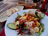 A zany but delicious salad and half of a tomato/mozzarella wrap
