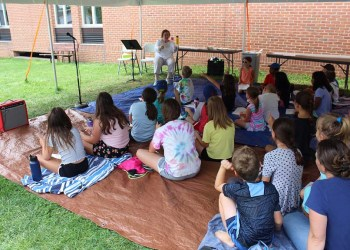 The packed Storytelling Camp crowd listens intently to reading specialist Mary Rys during the week of July 12-16, on the Dinosaur Garden lawn.