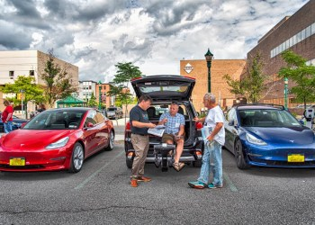 three middle-aged white men are gathered by three electric vehicles on a cloudy day