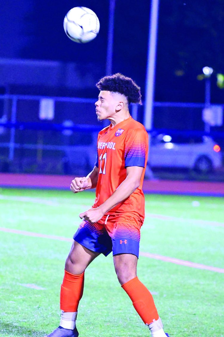 Liverpool defender Massimo Roja (11) puts his weight into a header during last Thursday's game against Fayetteville-Manlis. The Warriors lost to the Hornets 4-0.