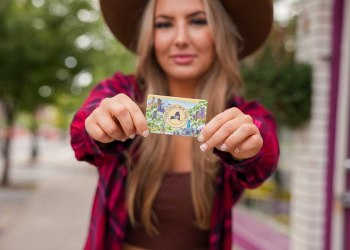 a white woman with blond hair wearing a tan hat and red flannel shirt displays the Eat Local New York card