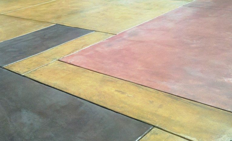A series of colored concrete rectangles--the floor slab of a house to come.