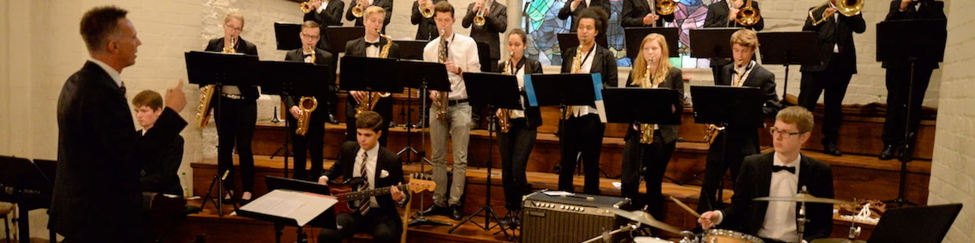 Altes Gymnasium Flensburg ensemble playing in front of a stained glass window.