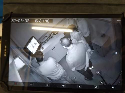 Imatge d'una càmera de seguretat en blanc i negre on es veuen 4 persones d'esquena mirant una televisió.