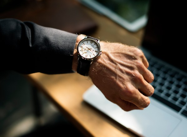 Man looming at watch, laptop in background