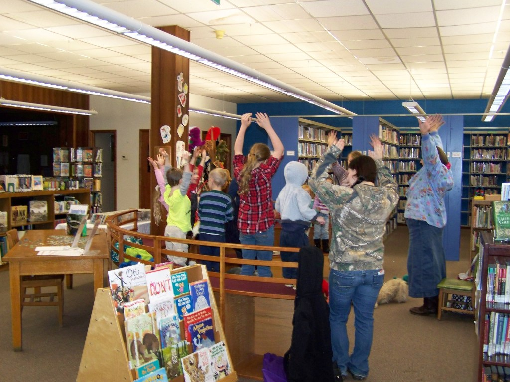 Children and adults stand and reach their arms up in a library