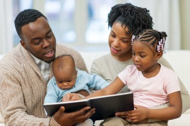 Two African-American parents read to their young children