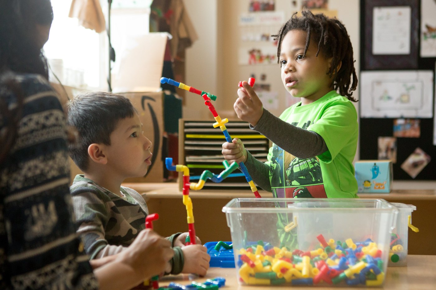 Preschool students build a structure with various interlocking pieces.