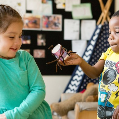 A preschool student shows his classmate a spider he made from pipe cleaners and a paper cup. www.deeperlearning4all.org/images