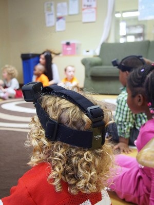A child wearing a GoPro on their head sits in a preschool circle with other children.