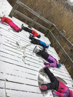 Children making snow angels on the deck