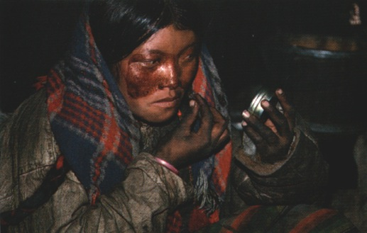 Nomad woman applying red face makeup
