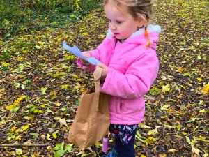 girl in pink jacket in the woods holding a scavenger hunt