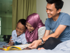 family - mum, dad and child reading a book together literacy