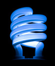 blue cfl light bulb against black background