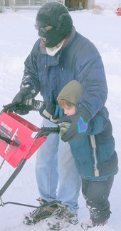 boy helping dad push snowblower