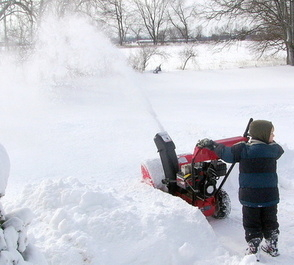 small boy using snowblower