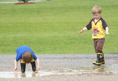 2 boys splashing in water puddle