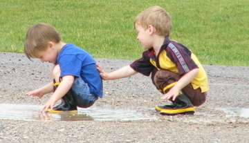 boy patting brother's back after putting mud in his pants