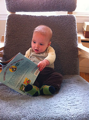 baby sitting on chair looking at book