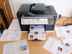 printer on table with lots of printouts scattered