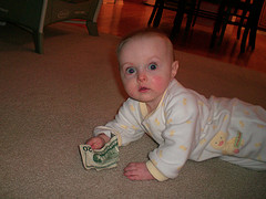 baby laying on floor holding twenty dollar bill